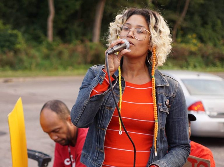 A photo of a person in a red shirt and jean jacket holding a microphone.