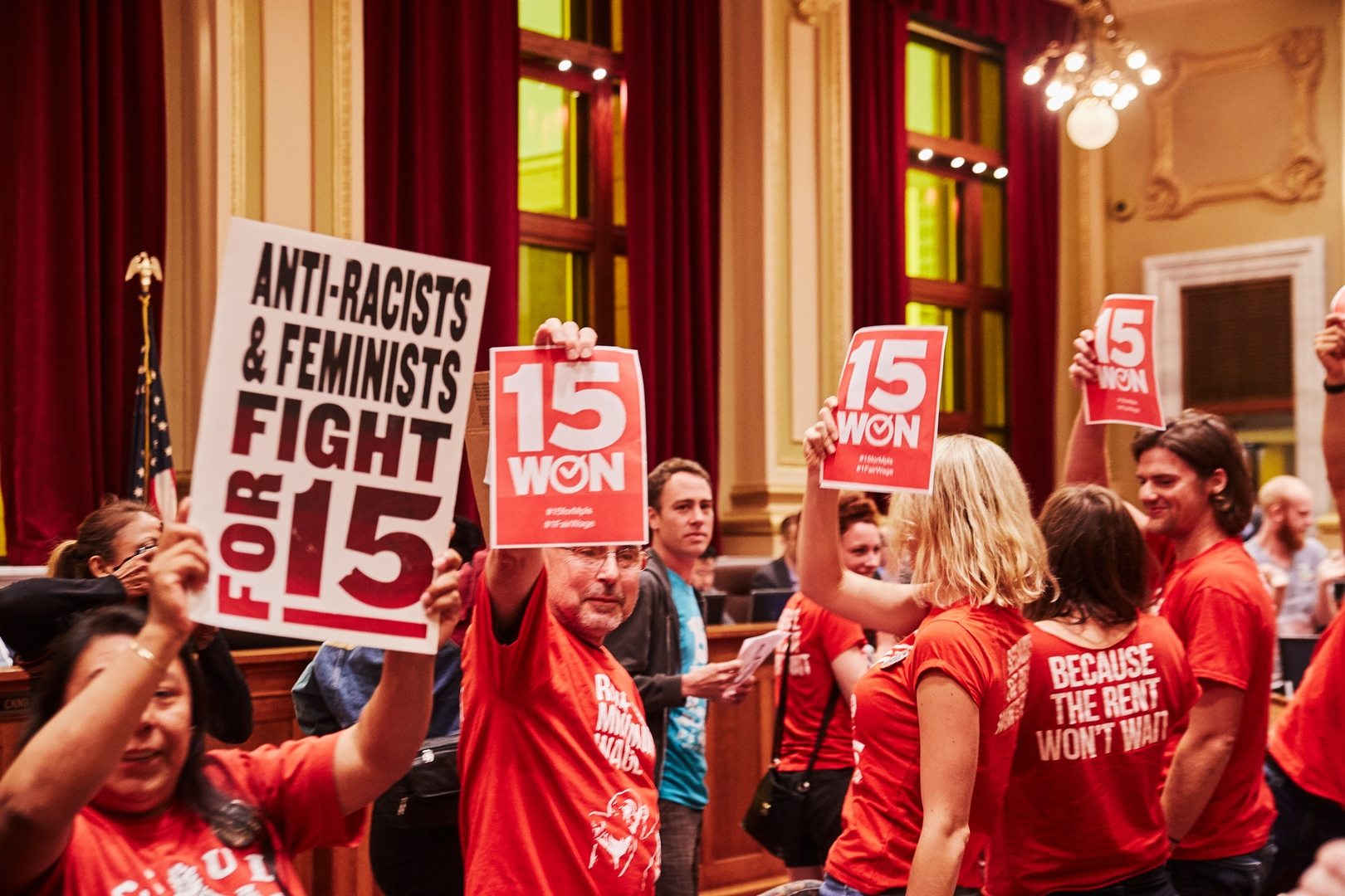 """A group of people in red shirts holding """"Fight for 15"""" signs."""
