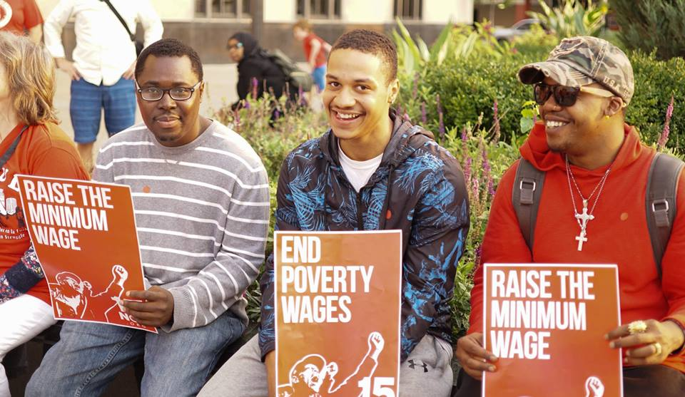 """A photo of some young men holding signs reading """"Raise the Minimum Wage."""""""