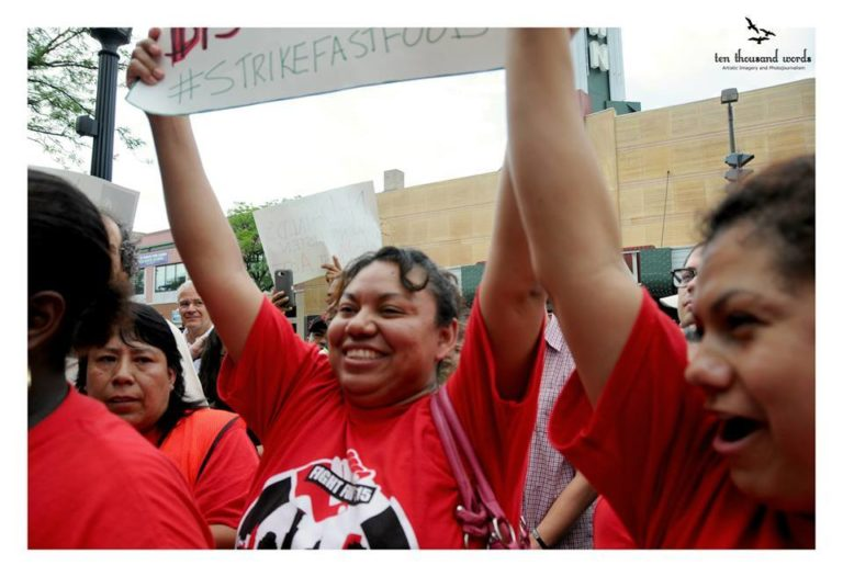 Workers in red CTUL shorts celebrate at a protest