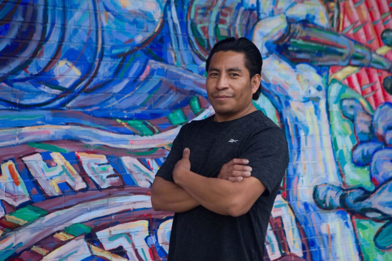 Photo of a man with arms crossed in front of a mural
