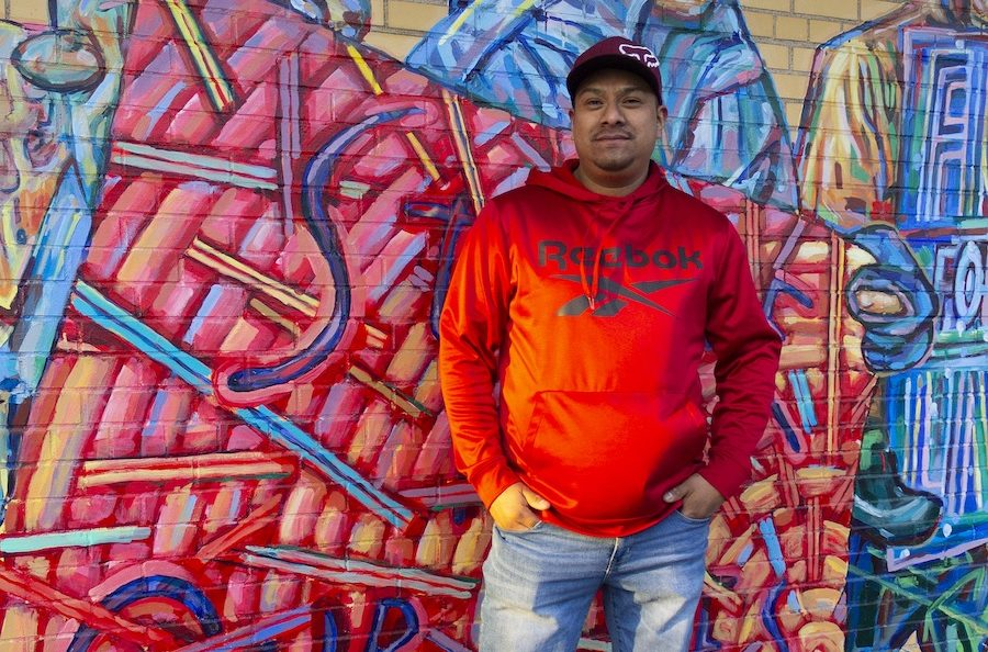 Man in a red shirt standing in front of a mural.
