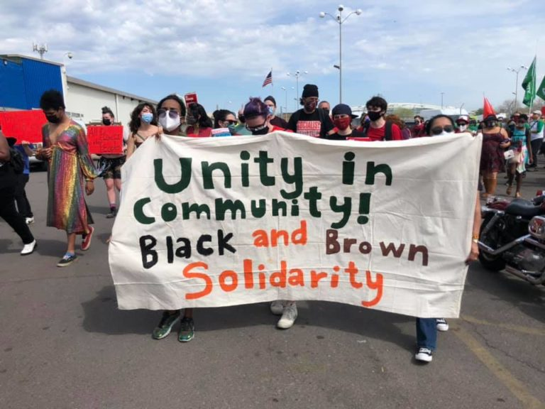 """CTUL staff and members hold a banner that reads """"Unity in Community! Black and Brown Solidarity"""" at the 2021 May Day March"""