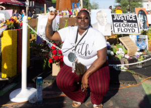 A woman crouching and raising a fist at George Floyd Square
